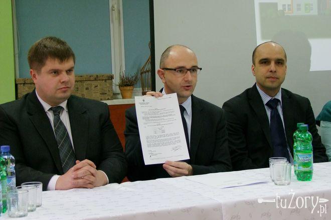 Wiceminister Adam Zdziebło prezentuje dokument potwierdzający przyznanie dofinansowania.